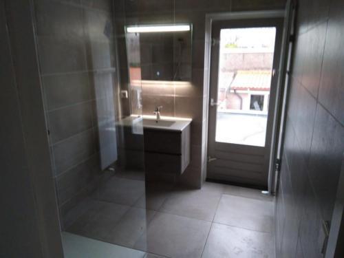 Badkamer, geheel betegeld, met leidingwerk en plaatsing. Overzicht