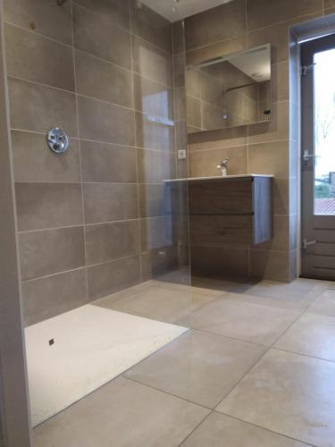 Badkamer, geheel betegeld, met leidingwerk en plaatsing. Deuraanzicht