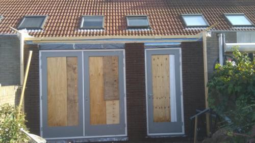 Buiten grotendeels gemetseld en de deuren en kozijnen zijn geplaatst